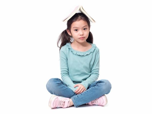 Bambina asiatica carina 6 anni seduto sul pavimento e metti il libro in testa. bambino adorabile prescolare con la copertina del libro sulla sua testa.