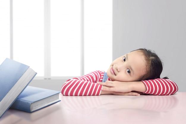 Bambina asiatica carina con i libri