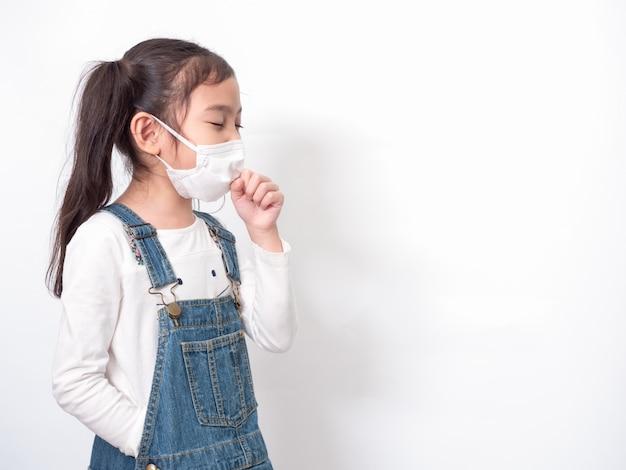 Bambina asiatica carina di 6 anni che indossa una maschera igienica per diffondere la malattia protettiva e tosse
