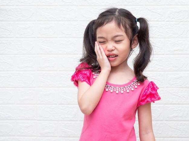 Bambina asiatica carina di 6 anni ha mal di denti e tiene sulla guancia.