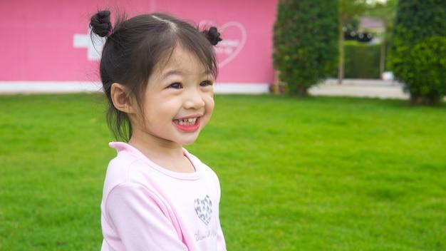 Bambina asiatica che corre e che cammina sul campo di erba.