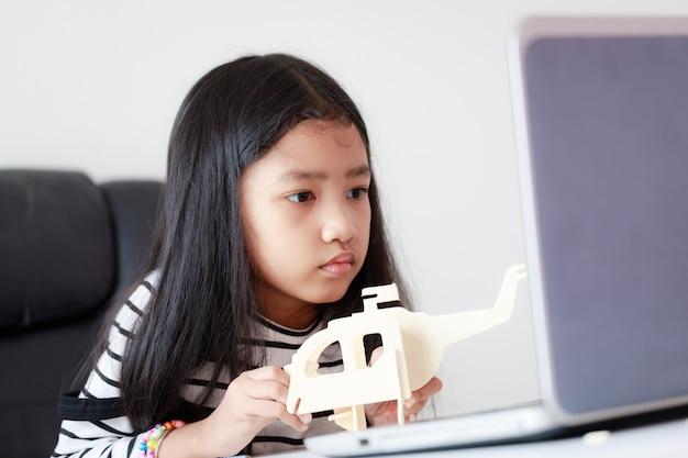 Bambina asiatica che elabora profondità di campo bassa del fuoco selezionato di modello di legno