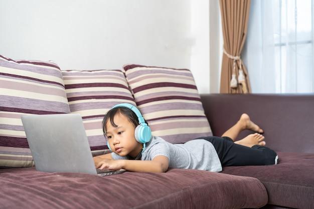 Bambina asiatica che per mezzo del computer portatile