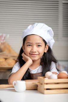 Bambina asiatica che porta un cappello bianco del cuoco unico e che sorride felicemente.