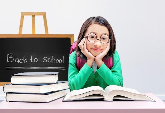Bambina asiatica con gli occhiali che legge il libro in classe