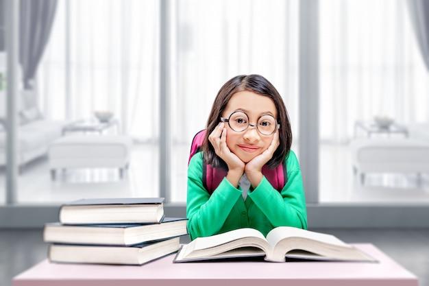 Bambina asiatica con gli occhiali che leggono il libro. torna al concetto di scuola