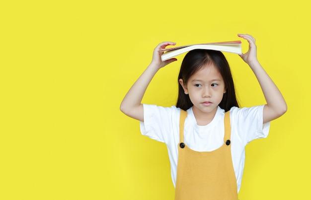 Bambina asiatica con un libro sulla sua testa