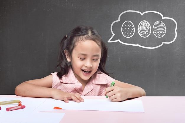 Bambina asiatica divertente con il pastello che disegna l'uovo di pasqua