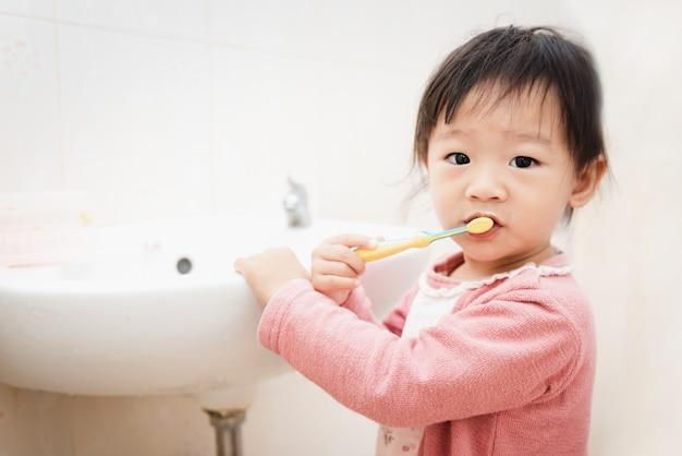 Bambina asiatica dolce del bambino che spazzola i suoi denti in bagno