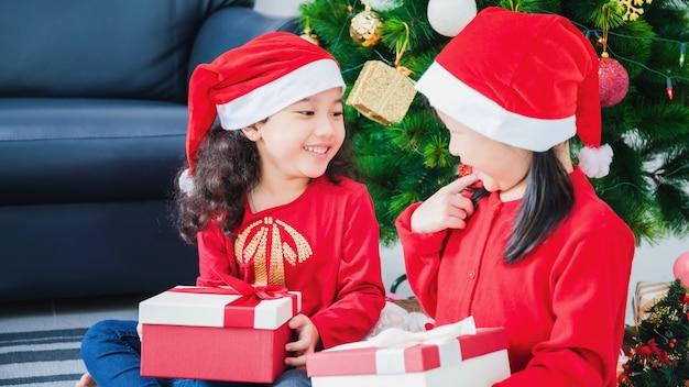Bambina asiatica ed amico che giocano e che decorano l'albero di natale nella stanza bianca a casa con il contenitore di regalo insieme fronte sorridente e felice di celebrare la festa del nuovo anno di festivel con la famiglia.