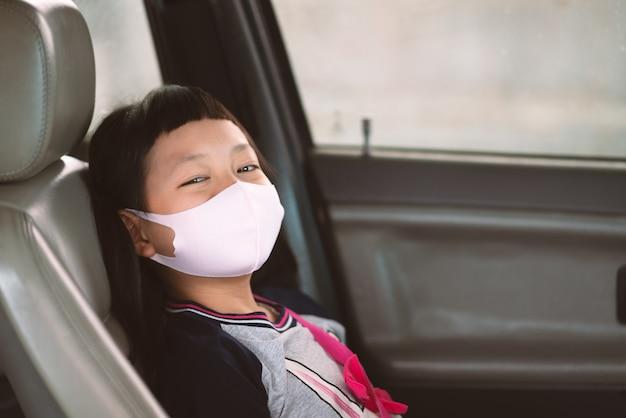 Bambina asiatica in una maschera di protezione da un finestrino della macchina. maschera igienica protezione coronavirus o covid-19