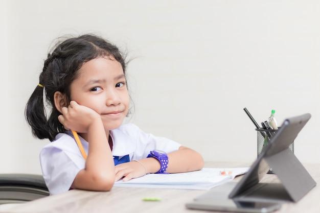 Bambina asiatica in uniforme dello studente che fa i compiti