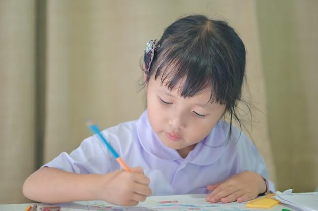Bambina asiatica in uniforme prescolare che fa il disegno e la pittura di compito della scuola