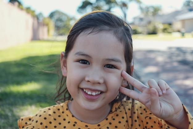 Bambina asiatica mista felice e in buona salute sveglia che indossa il pois giallo