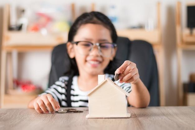 Bambina asiatica nel mettere moneta dentro per alloggiare porcellino salvadanaio