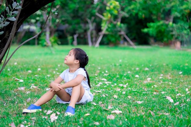 Bambina asiatica sveglia che si siede nel parco e alzò lo sguardo