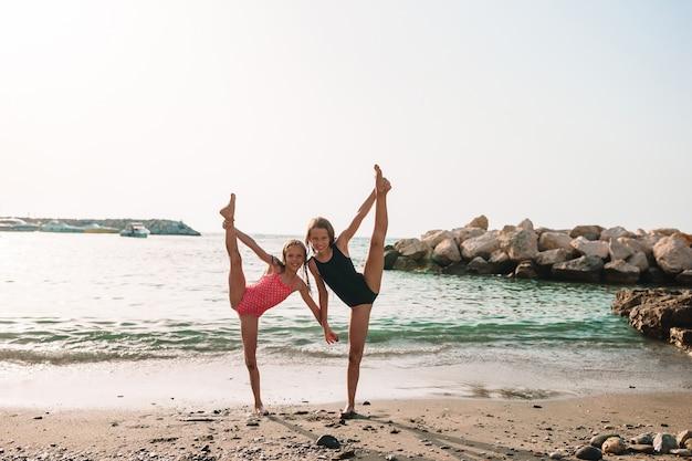 Bambina attiva in spiaggia divertendosi molto. ragazzo carino fare esercizi sportivi in riva al mare