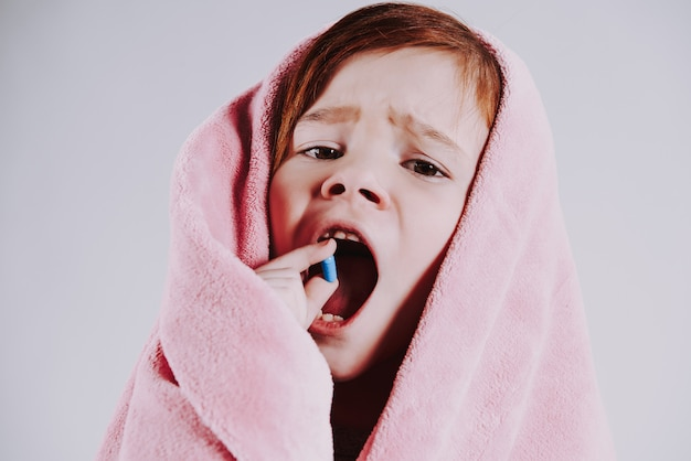 Bambina avvolta nella coperta, usa le medicine.