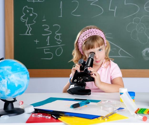Bambina bambina in classe scuola con microscopio
