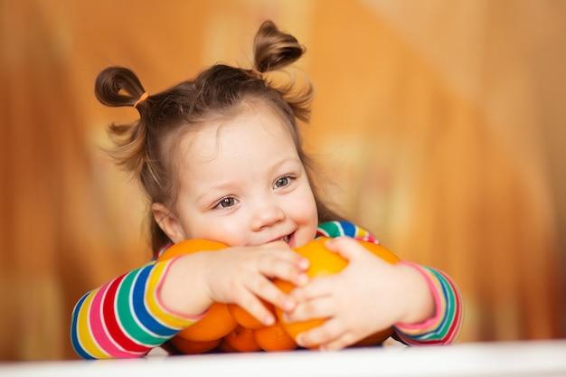 Bambina, bambino di 3 anni, con una pettinatura a coda di cavallo in una colorata giacca a righe colorate abbraccia un sacco di appelsins