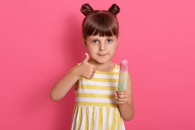 Bambina bambino felice e mostrando il pollice in su