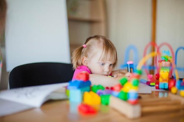 Bambina bella seduta alla scrivania scrivania
