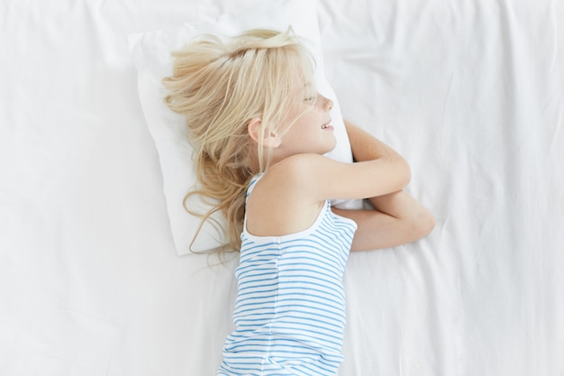 Bambina bionda carina nel letto bianco