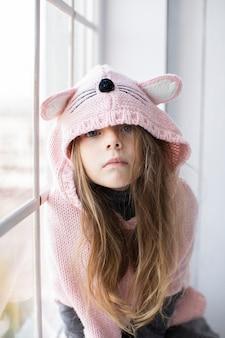 Bambina bionda che indossa pullover rosa