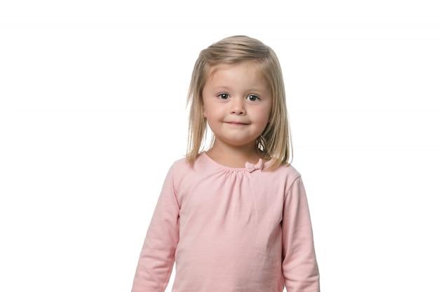 Bambina bionda che sorride alla macchina fotografica su fondo bianco