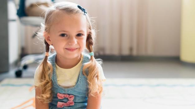 Bambina bionda che sorride con lo spazio della copia