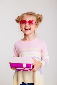 Bambina bionda che sorride in occhiali da sole a forma di cuore rosa che tengono un contenitore di regalo rosa su un fondo bianco