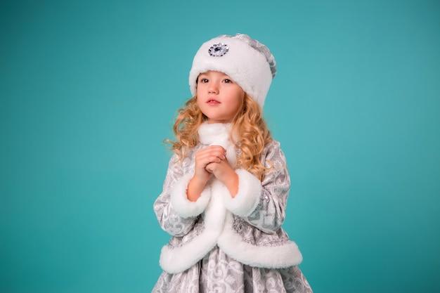 Bambina bionda che sorride nell'isolato del costume da nubile della neve sulla parete blu