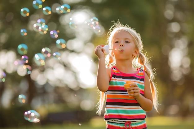 Bambina bionda gonfia le bolle di sapone in estate in una passeggiata