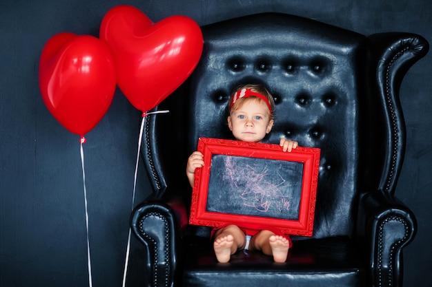 Bambina bionda in abito rosso con ghirlanda rossa con cuori seduto sulla poltrona con palloncino cuore rosso il giorno di san valentino.