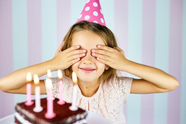 Bambina bionda in berretto da compleanno rosa sorridente, chiudi gli occhi, esprimi un desiderio, sorprendi una torta di compleanno al cioccolato con candele. la bambina festeggia il suo compleanno.
