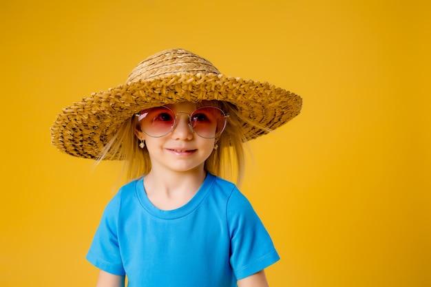 Bambina bionda in occhiali da sole e un cappello di paglia in abiti blu su uno sfondo giallo di isolare