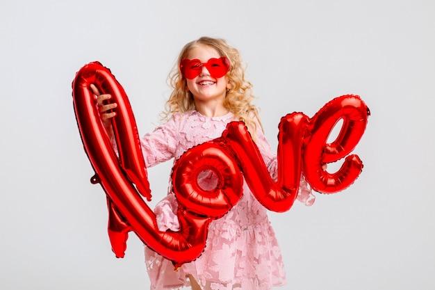 Bambina bionda in un abito rosa tiene in mano la scritta