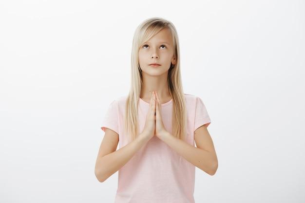 Bambina bionda speranzosa che prega dio, supplica