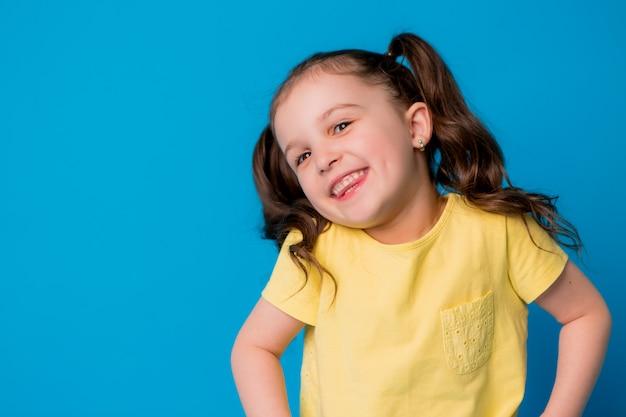 Bambina bruna su sfondo blu, sorridente