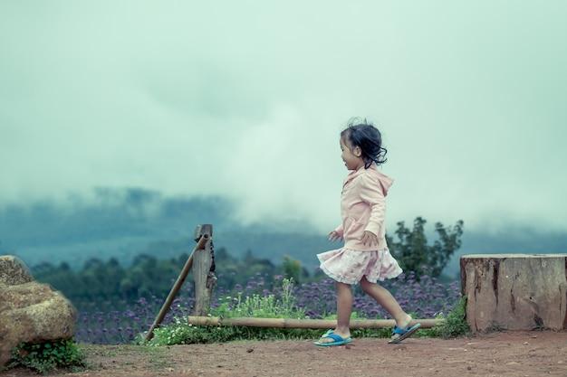 Bambina carina bambina che corre in giardino dopo la pioggia