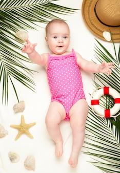Bambina carina con accessori da spiaggia. feste in mare con il bambino, concetto di estate
