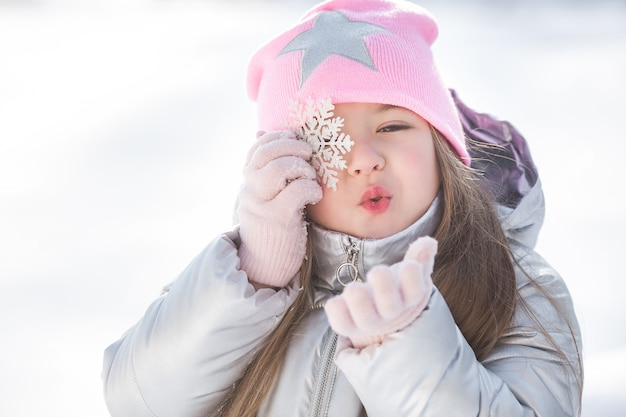 Bambina carina con fiocco di neve
