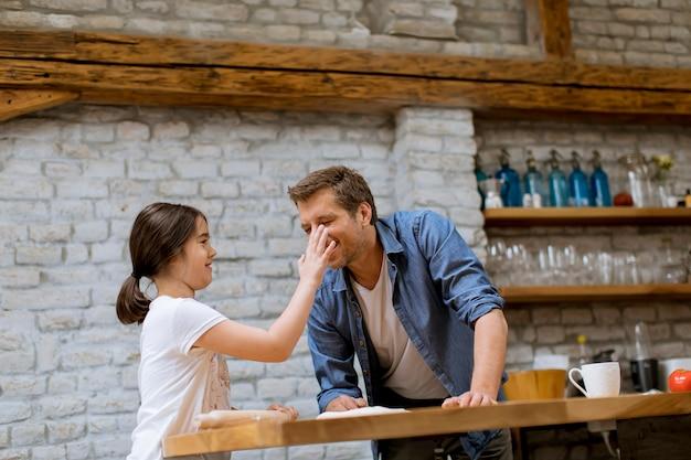Bambina carina e il suo bel papà preparare la pasta in cucina