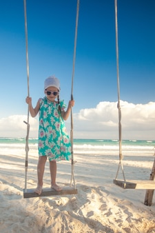 Bambina carina in abito cavalcando un'altalena sulla spiaggia