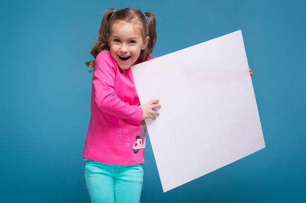 Bambina carina in camicia rosa con scimmia e pantaloni blu tenere cartello vuoto vuoto