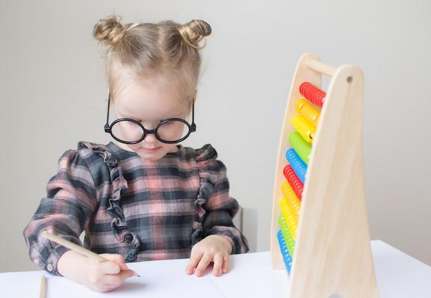 Bambina caucasica con gli occhiali rotondi. piccola maestra. umorismo divertente con gli occhiali. stile retrò
