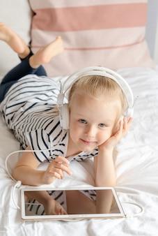 Bambina caucasica in cuffia che guarda il tablet a letto, interni domestici, moderne tecnologie dei dispositivi stile scandinavo