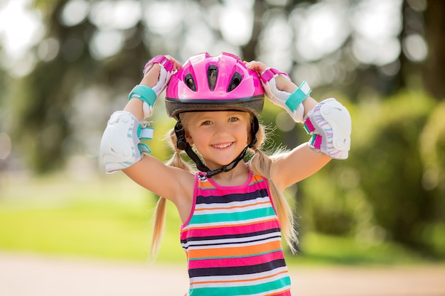 Bambina cavalca su pattini a rotelle in estate in un parco cittadino
