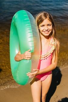 Bambina che abbraccia il tubo di aria piscina