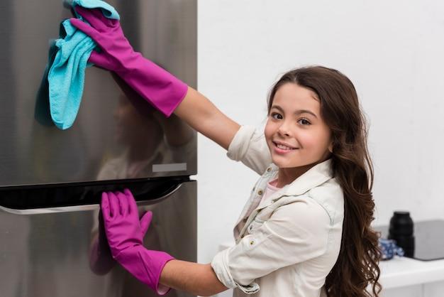 Bambina che aiuta sua madre pulendo la cucina